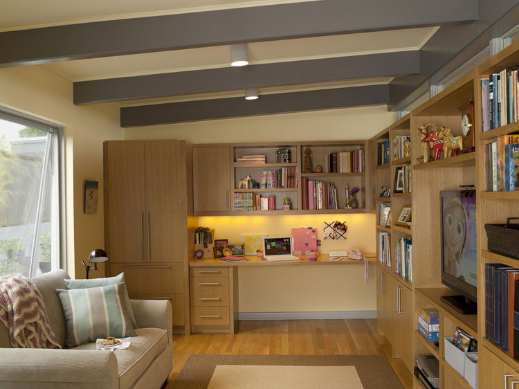 The new family room has a built-in desk for the daughter, who often uses the room to hang out with friends. The kitchen is just on the other side of the wall at right and shares its row of interior clerestory windows.
