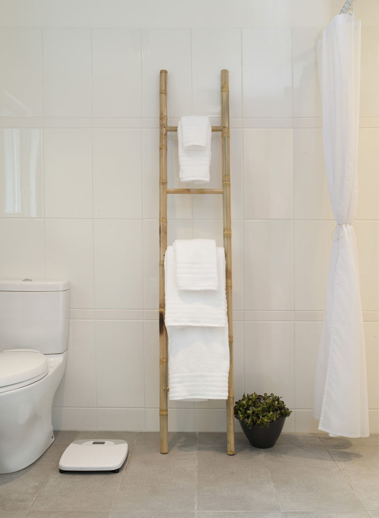 A simple bamboo ladder holds towels in the master bathroom, whose floors are radiant-heated. Just beyond the curtain at right is the curbless shower. Toto toilet.