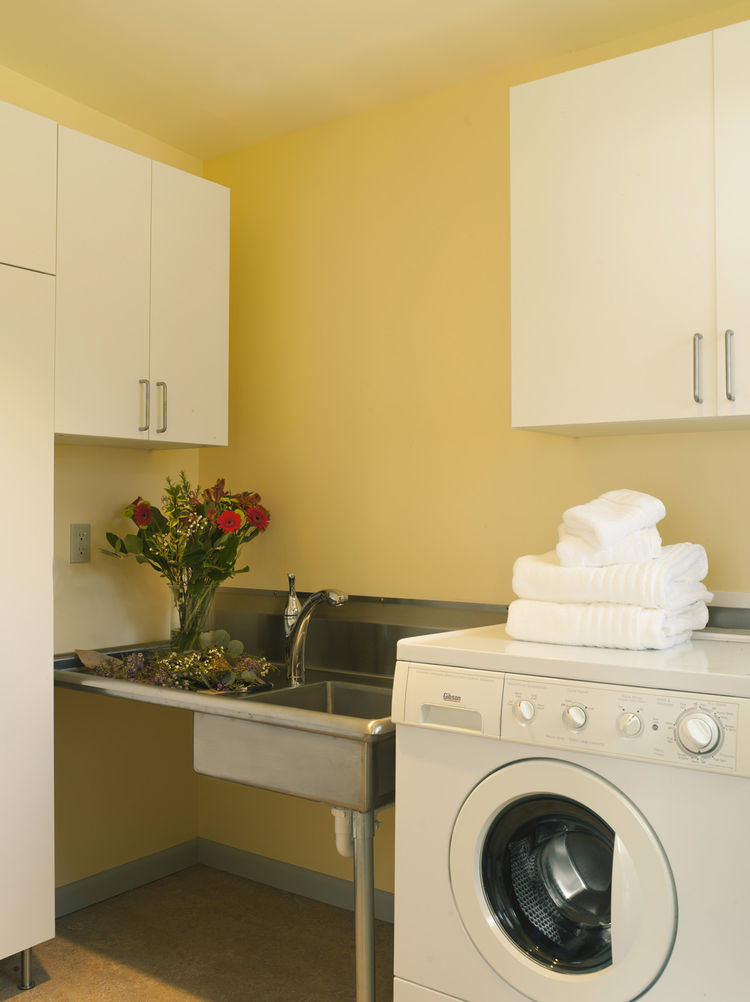"Near the front-loading machine in the laundry room is a utility sink Braitmayer found at a restaurant supply store; she had the legs cut to her height specifications. The cabinets are from IKEA. ""Happy colors are really important in Seattle, because it's"