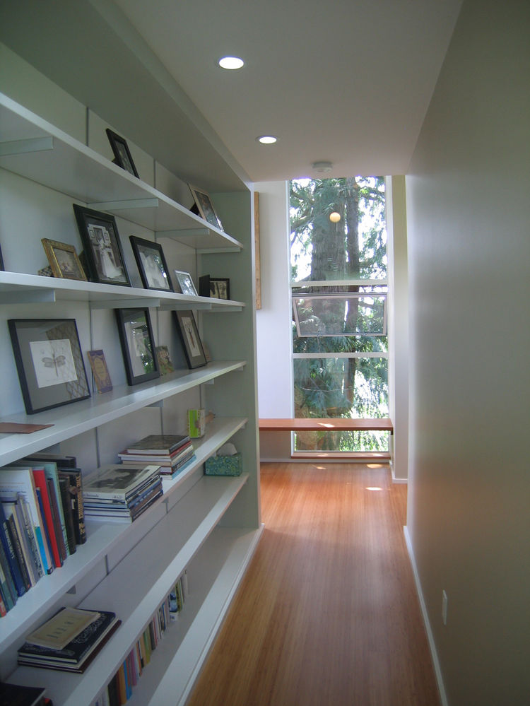 A long bookcase connects the master bathroom to the bedroom.
