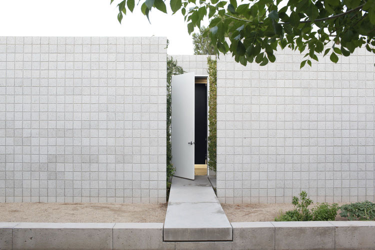 The front door is accessed by a 'floating' concrete bridge that bisects the two wings of the house.
