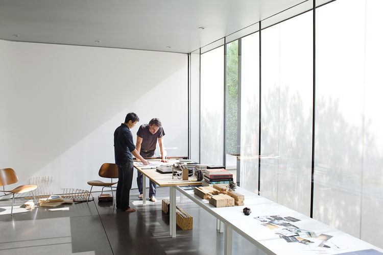 "Atherton and Keener review architectural drawings in their ""living room,"" which also serves as a work studio and performance space."