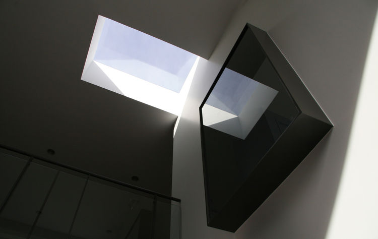 Prominent black pop-out windows constitute one of the house's more distinguished features. The windows are constructed of 3/8-inch steel and flush-mounted glass, offering outside viewers a mirrorlike reflection of the sky.