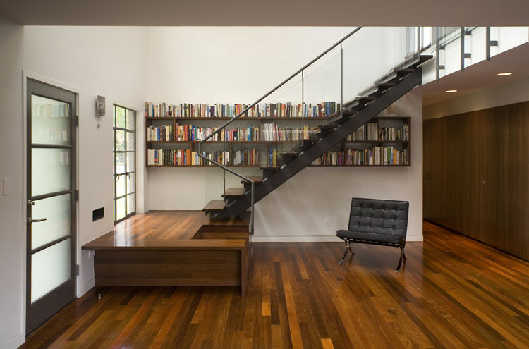 """Particularly fond of careful detail, Alter designed the treads of the entryway staircase to merge seamlessly into the adjacent bookshelves. """"I enjoy doing things that make you wonder about the context and look a little further,"""" he says."""