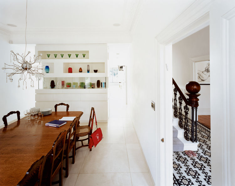 """""""I like the idea of houses having layers,"""" says Phillips, who incorporated the home's strong traditional features into his design. He kept the formal dining room, for example, which is divided from the kitchen by an elegant cabinet displaying colorful gla"""