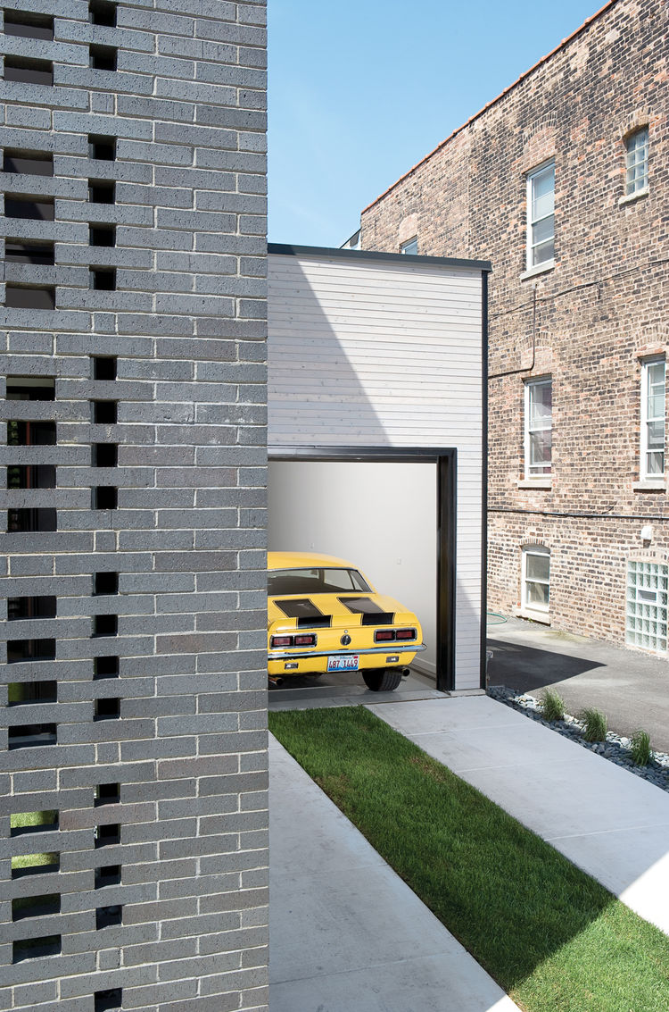 When open, the garage enables the owners to work on their vehicles while visiting with neighbors who do the same.