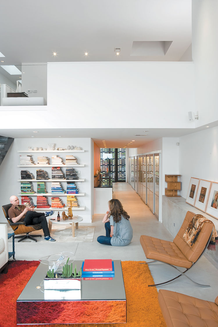 Hernandez and Surratt relax in the living room, which is enlivened by the house's internal topography. A short flight of steps divides the interconnected areas and offers a place to sit. Above is a loft that can be converted to a bedroom.