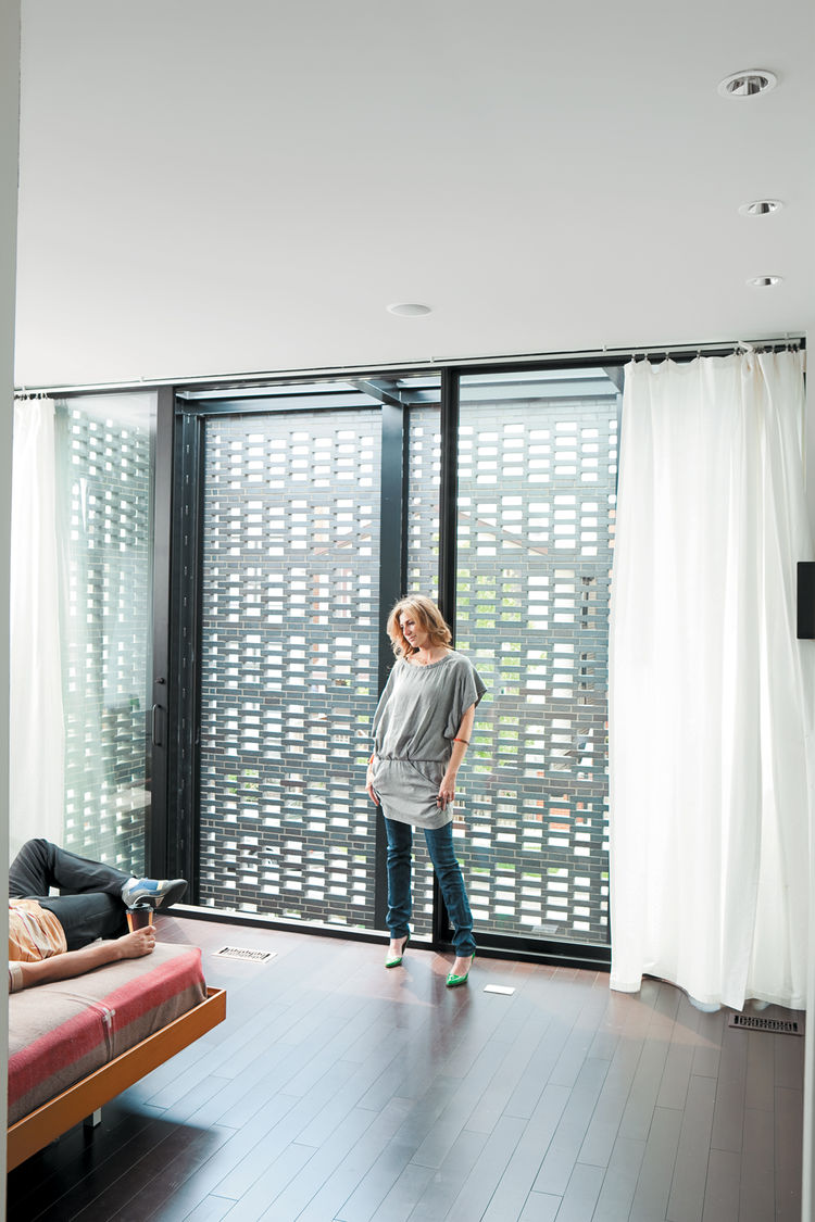 In the master bedroom, the couple enjoy the ample natural light that filters through the brick screen.