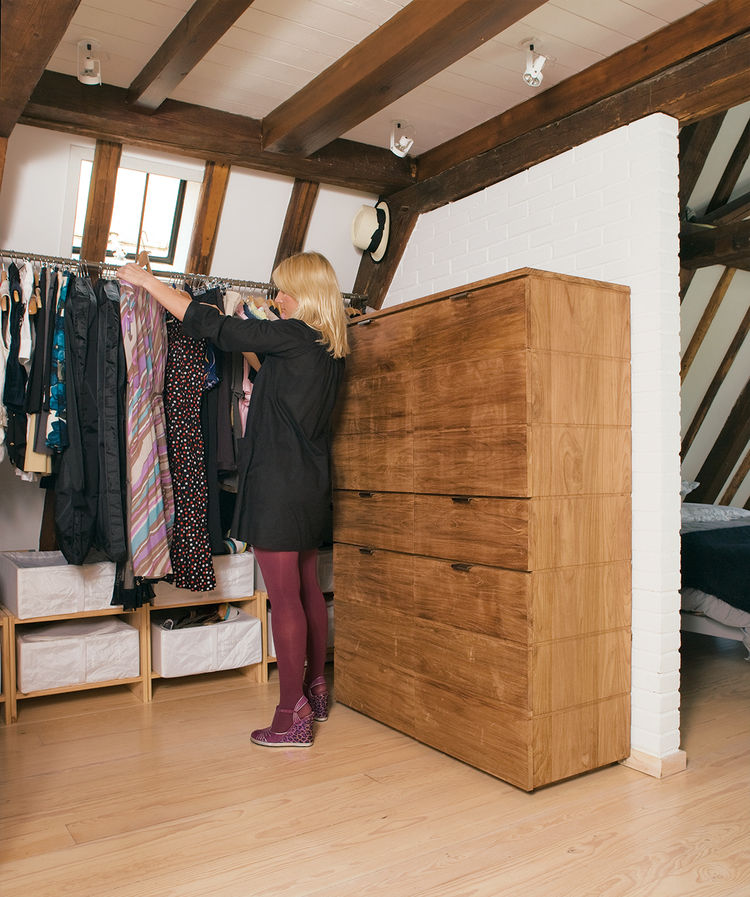 Few structural additions were made to the apartment, but the half wall in the top-floor bedroom was one of them The wall and an elegant chest of drawers by Peter Laszlo create storage for clothes without breaking up space. The white-painted brick of the n
