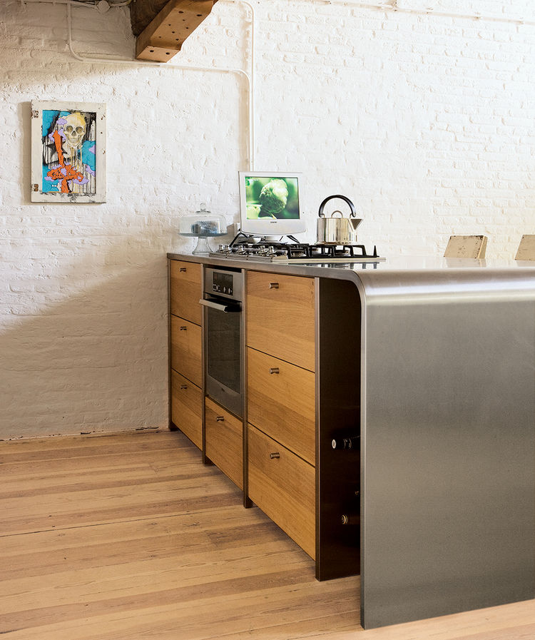 "Teak cabinets add warmth to the steel counter in the kitchen, which local designers Op16 created for the couple. The picture was created by the New York graffiti artist Cycle and was purchased at <a href=""http://www.upperplayground.com/"">Upper Playground<"