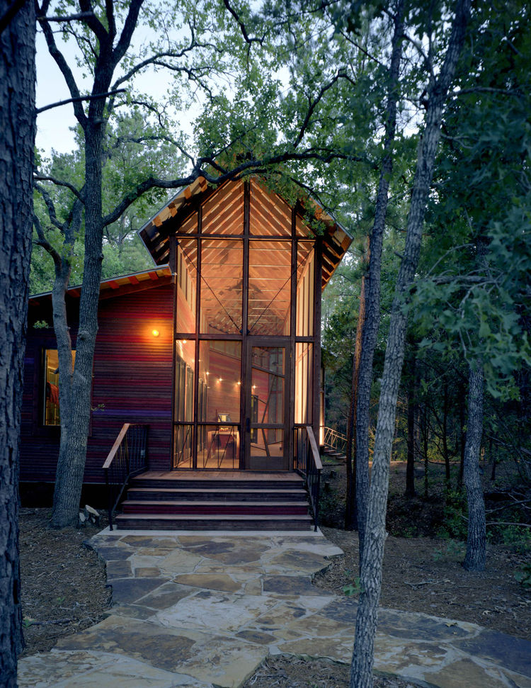The architectural relationship between the bunkroom and porch, and the bunkhouse and the surrounding forest, is especially apparent at dusk, when the building reads as a kind of illuminated lantern.