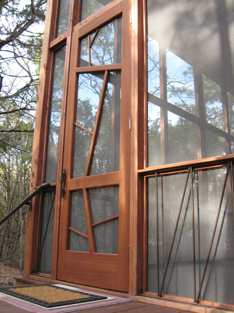 "The nine-by-three-foot mahogany entrance door is meant to evoke the surrounding trees. The iron handrails lining the base of the porch are a subtle architectural detail, as well as a support system to prevent the cabin from ever twisting or shifting ""like"
