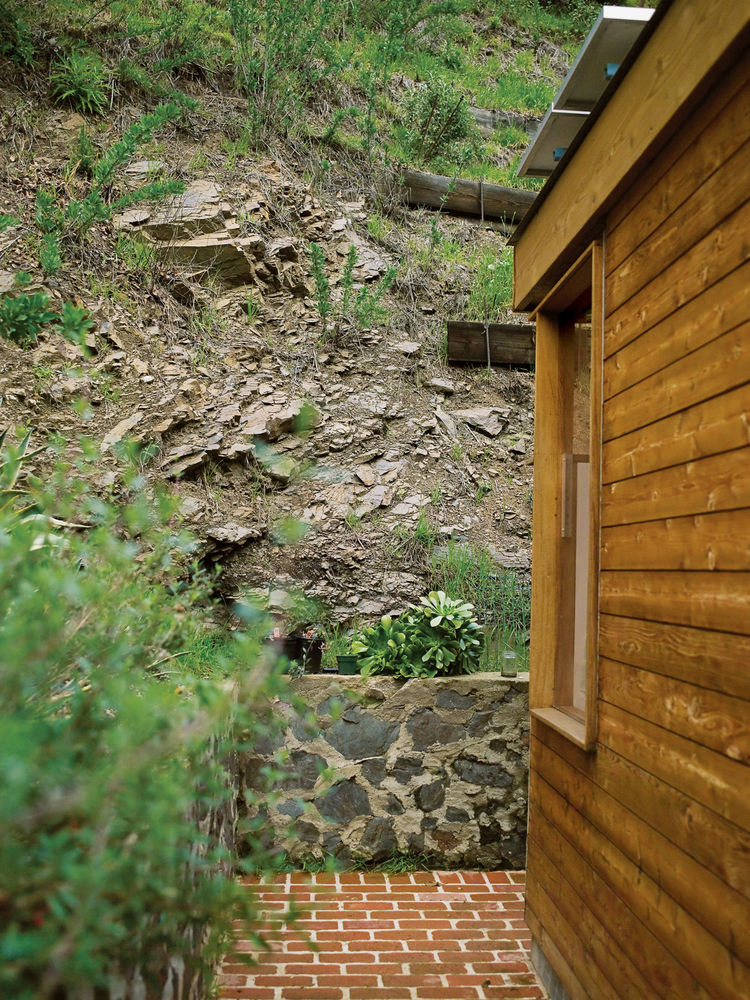 The steep canyon wall rises directly behind the house.