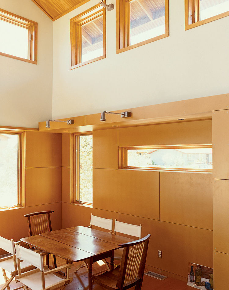 Light pours into the Ankneys' living/dining area with its clear pine plywood ceiling, clear-finish MDF paneling on the walls, and reclaimed-fir flooring.