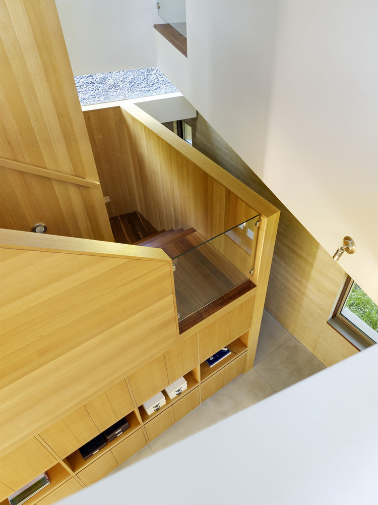 The stairwell is a key feature in the home. It's located in the back of the house so that people are drawn into the interior spaces and can interact with whoever is home. The stairwell also houses a hefty amount of storage. All of the cabinetry was design