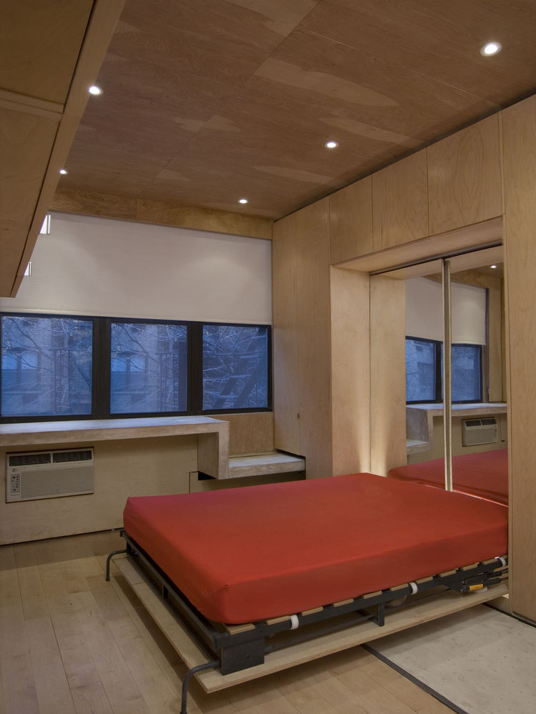 "The Murphy bed in its pulled-down state is backed by mirrors from <a href=""http://www.sergisimages.com"">Sergi's Images Mirrors & Glass</a> to help bounce light from the north-facing windows around the apartment. A cabinet hung at the upper left provides m"