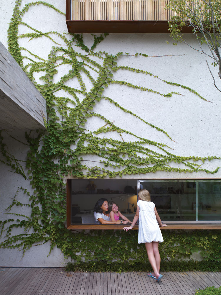 From the garden deck, Sophia Cóser talks to sister Helena and mother Piti through a wide, low-slung window typical of architect Marcio Kogan.