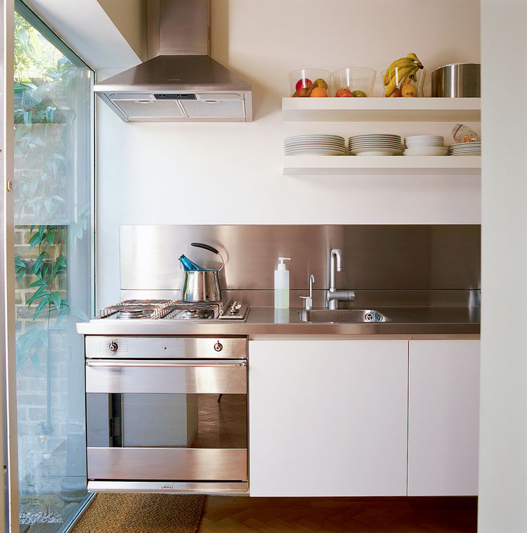 """""""You can stand in one space and reach everything,"""" explains Colin of the precise kitchen layout with its custom-made stainless steel countertop, cantilevered cupboards, and integrated cooktop and oven. The cupboards' shallow shelves were specially made to"""