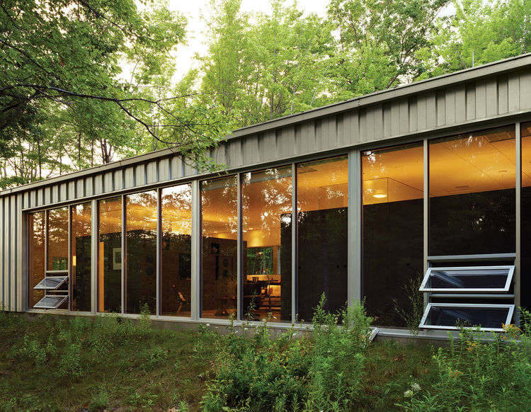 "Floor-to-ceiling windows capture natural light and warmth while offering expansive views of the woods to the south. ""In the winter, I like to use the house as therapy because there's so much light,"" Cook says."