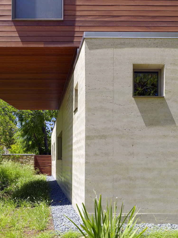 """We originally proposed using concrete for the walls because we like the plain style and directness,"" the owners say. Instead of concrete, Smith suggested rammed earth, a material that combines some of the physical properties of concrete, but is less ""psy"