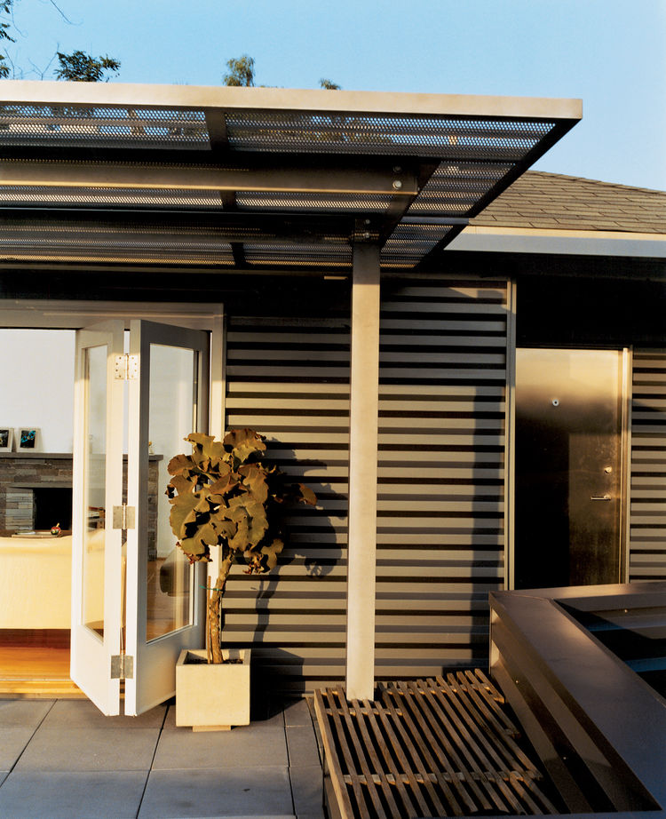 Day skinned the house in ­corrugated-aluminum siding, a tough industrial palette he picked up while designing airports. The corrugated stainless steel canopy was fabricated by Day's former SCI-Arc classmates.