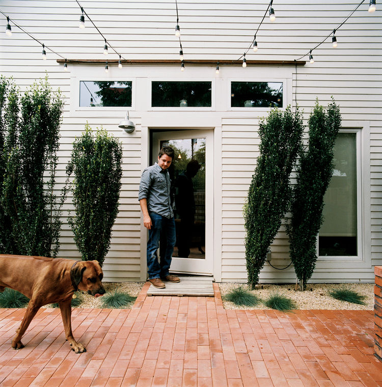 From the side door of his restored two-bedroom bungalow, Dollahite watches his  dog West inspect the newly installed low-maintenance landscaping and brick patio.