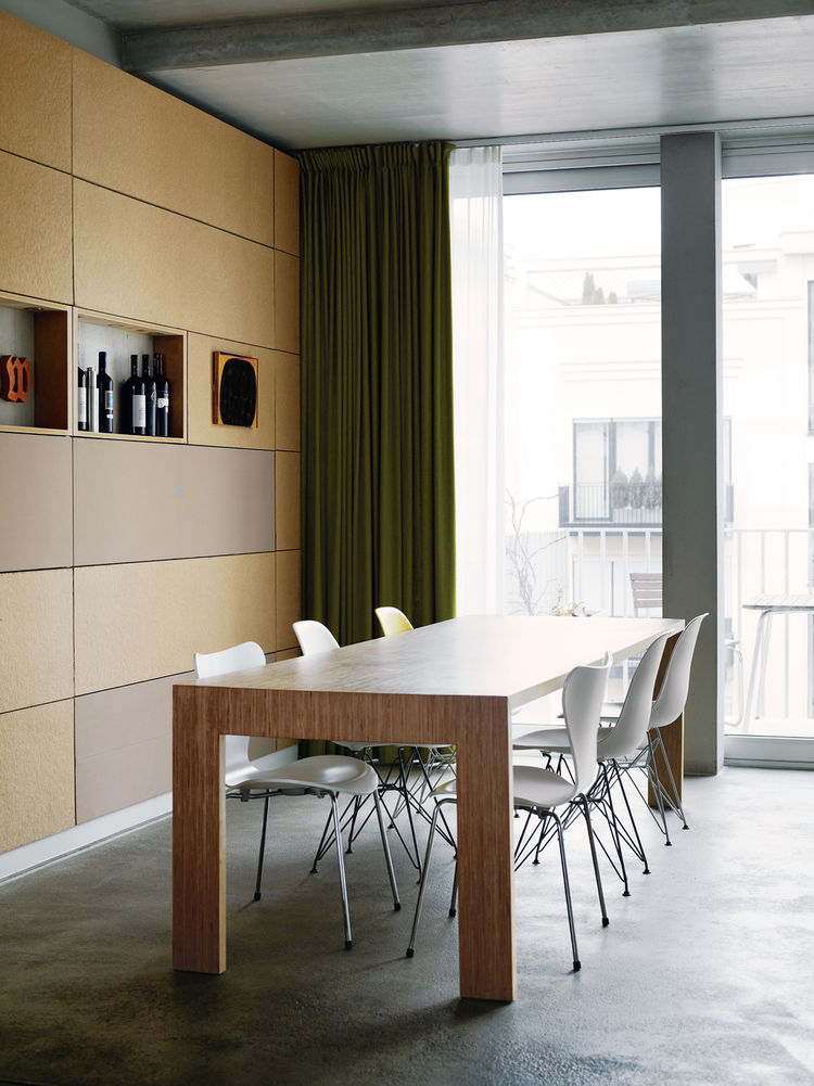 Next to the kitchen, Eames and Jacobsen chairs welcome dinner guests to the dining-room table. The back wall is covered in particleboard panels.