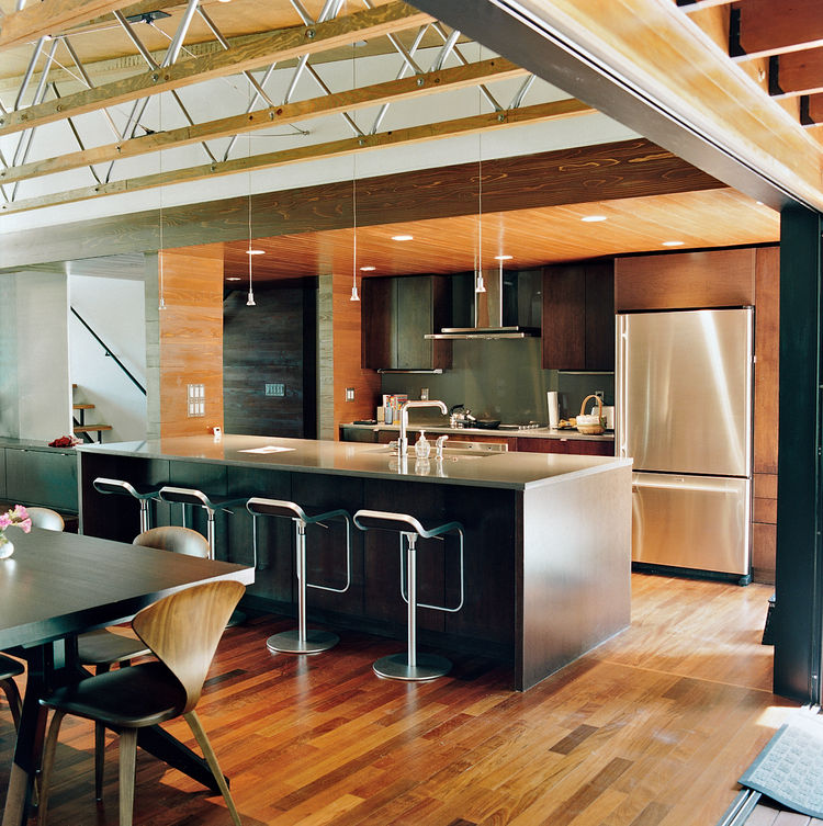 The couple opted for a smaller kitchen without fussy appliances and a larger dining area. They concentrated on achieving a high-quality space through carefully chosen furnishings, including the Cross Extension table in wenge a Cherner side chair, and the