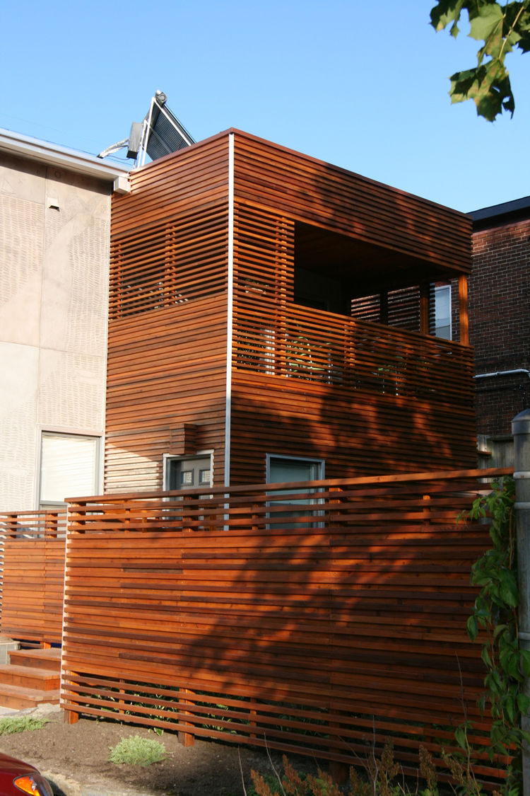 The architect used horizontal slats for privacy, but alternated them on the fence and second-floor deck to allow sunlight and breezes through. Solar panels atop the roof heat the water; a green roof is in the process of growing in. The project was awarded
