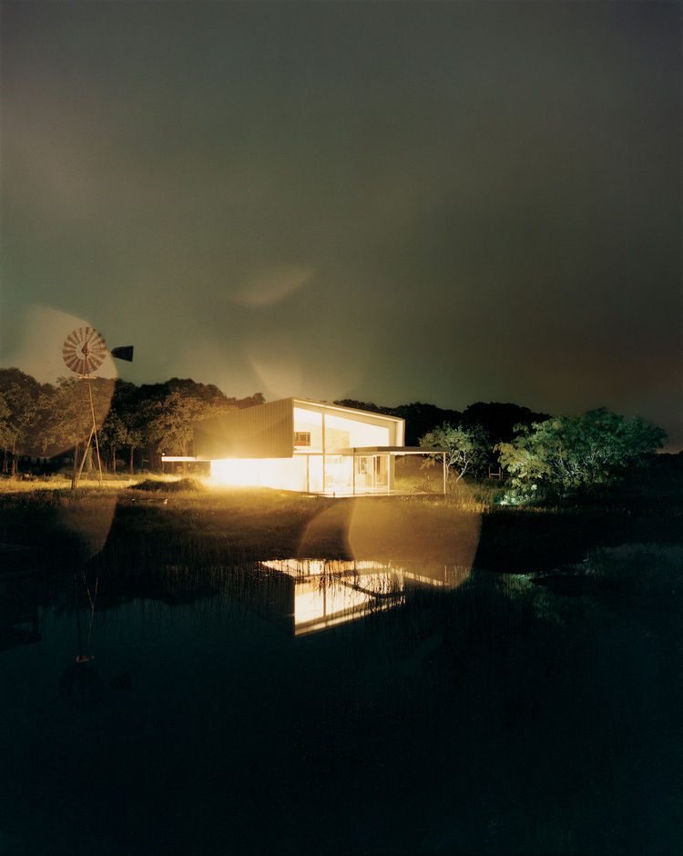 glowing home reflected on water Texas countryside