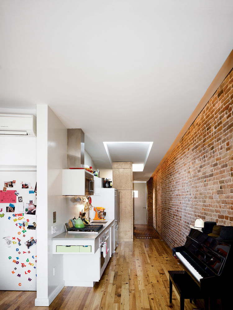 From the living room, the narrow apartment stretches back into the sleeping quarters by way of a compact kitchen that packs all the needs of a home chef against one wall.