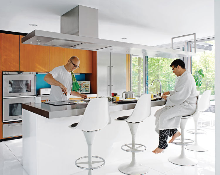Despite their fidelity to the original structure, the residents made small changes, notably in the kitchen: The wood-veneered island was moved to create more circulation space behind it and finished in white lacquer and stainless steel. Wood cabinetry abo