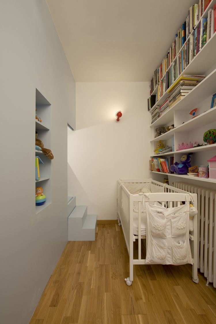 When baby Jean is older, he'll join older sister Eva in frolicking in and around the nooks and crannies of the partition. For now, however, he sleeps in this compact space with room for his crib, books, and toys. A small window with a sliding shutter plac