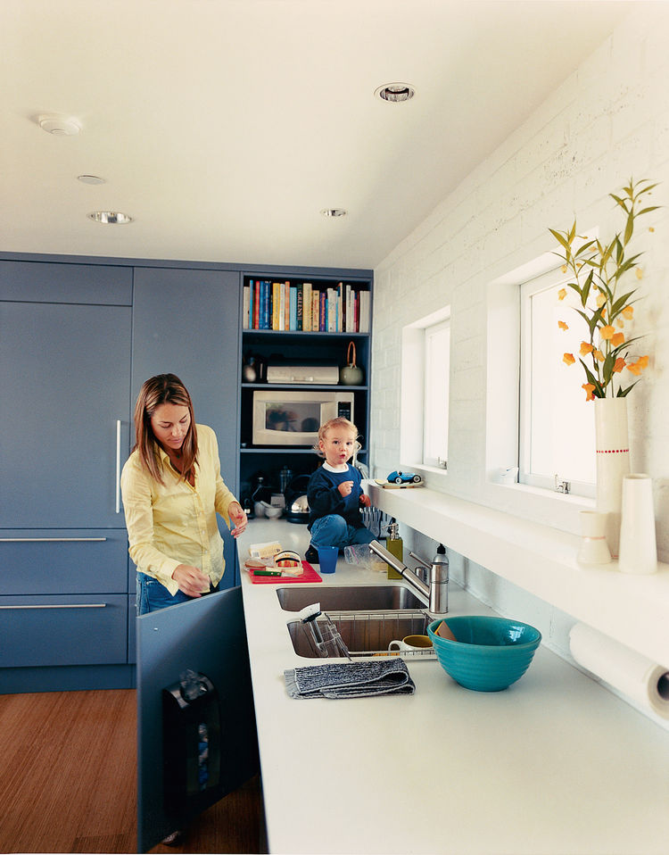 Julie enjoys her new kitchen with son Emerson. She wanted to conceal as many appliances as possible, so Deam disguised the Sub-Zero refrigerator and Miele dishwasher with panels from Downsview Kitchens that match the cabinets, giving the kitchen a clean,