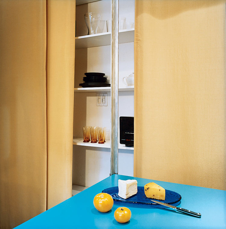 Hughston keeps all his tableware behind the curtain, on the shelves nearest the kitchen. The ample shelf space, covering the entire wall (except that taken up by the Murphy bed), makes it easy for Hughston to avoid mess. The contrast of gold and turquoise