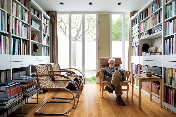 The library is lit by the front courtyard. The chartreuse vent, originally painted vermilion, is the one architectural color inside the house. Two Cantilever Cane chairs by Mies van der Rohe face Isaacson as he rests upon a Pernilla easy chair by Bruno Ma
