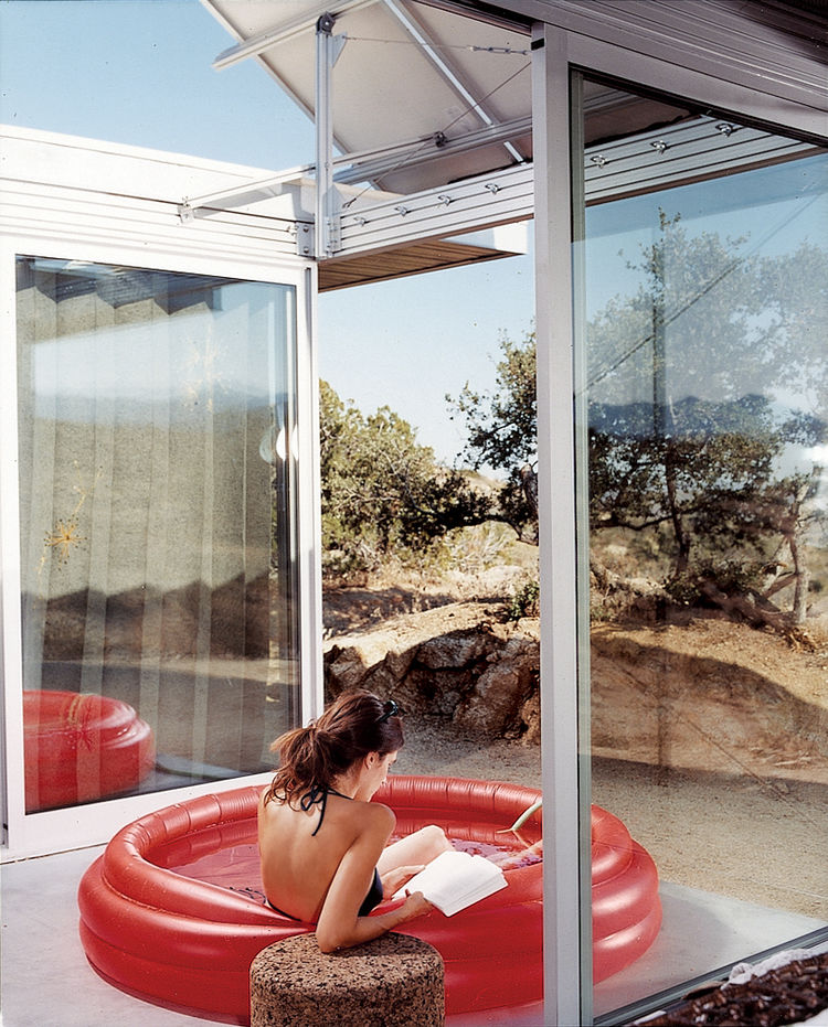 "The living space and bedrooms are separated by two small courtyards. Linda Taalman reclines in a small, inflatable wading pool in the home's ""firecourt,"" facing south toward the desert."