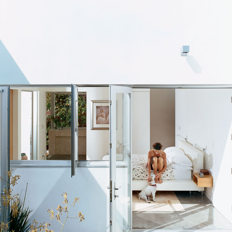 The house is clad in smooth stucco top-coated with white Venetian plaster.