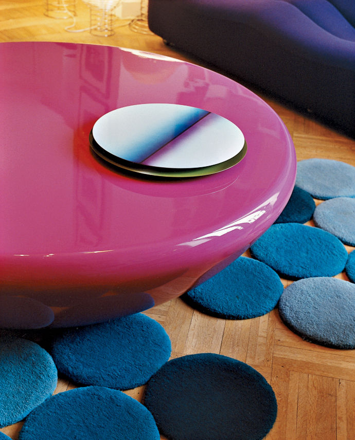 The bright pink Smarties table by Mattia Bonetti is surounded by designs by the Bouroullec brothers—a lacquered steel table center and blue rug.