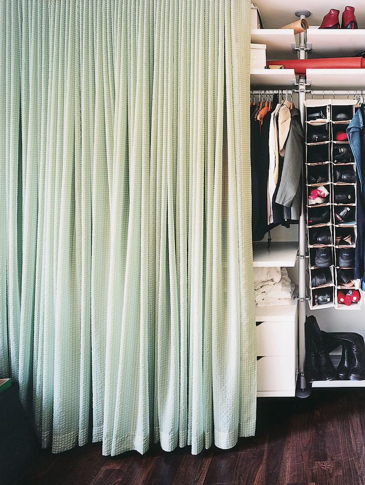 The contents of the 15-foot-long closet, concealed by a long swath of calming blue-green fabric, glows like a light box when illuminated from within.