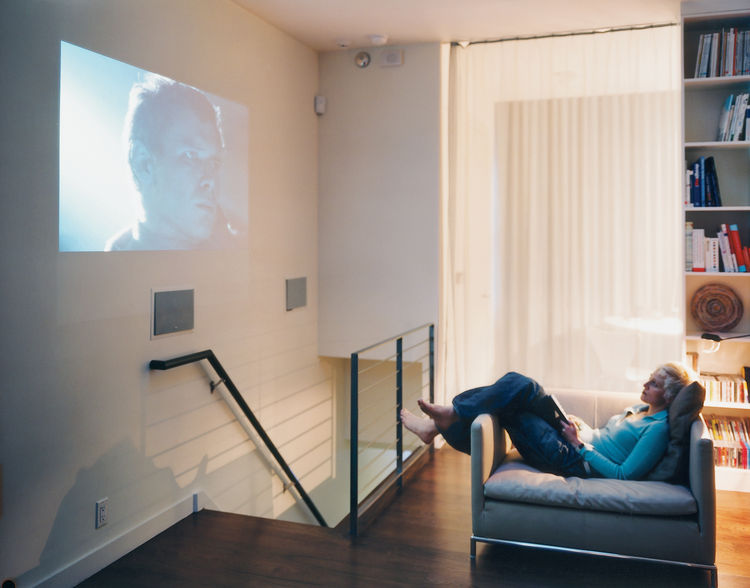 Wireless wonderland: One way to reduce clutter is by stashing most of the media hardware downstairs and jettisoning the television. When it's time to show a DVD, the wall does double duty as a movie screen.