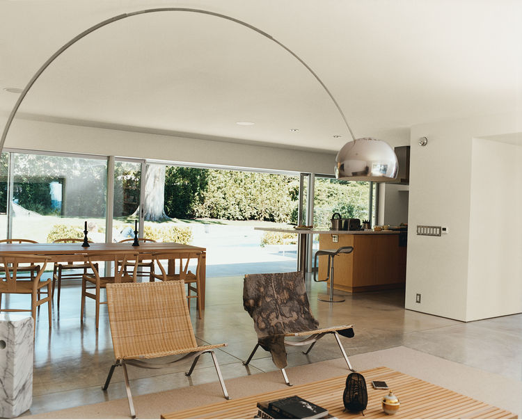 A 14-foot-wide opening at the rear of the house contributes, along with the concrete flooring, to an almost seamless transition from indoors to the patio. A spate of mid-century furnishings includes chairs by Hans Wegner and Poul Kjærholm and an Achille C