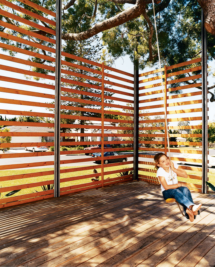 Gabriella swings on the rope swing hung from the podocarpus tree. The twenty-foot-tall, steel-framed, custom-built wood screen provides enough privacy to give the outdoor space the feeling of a room, with the 50-year-old polocarpus tree acting as a roof.