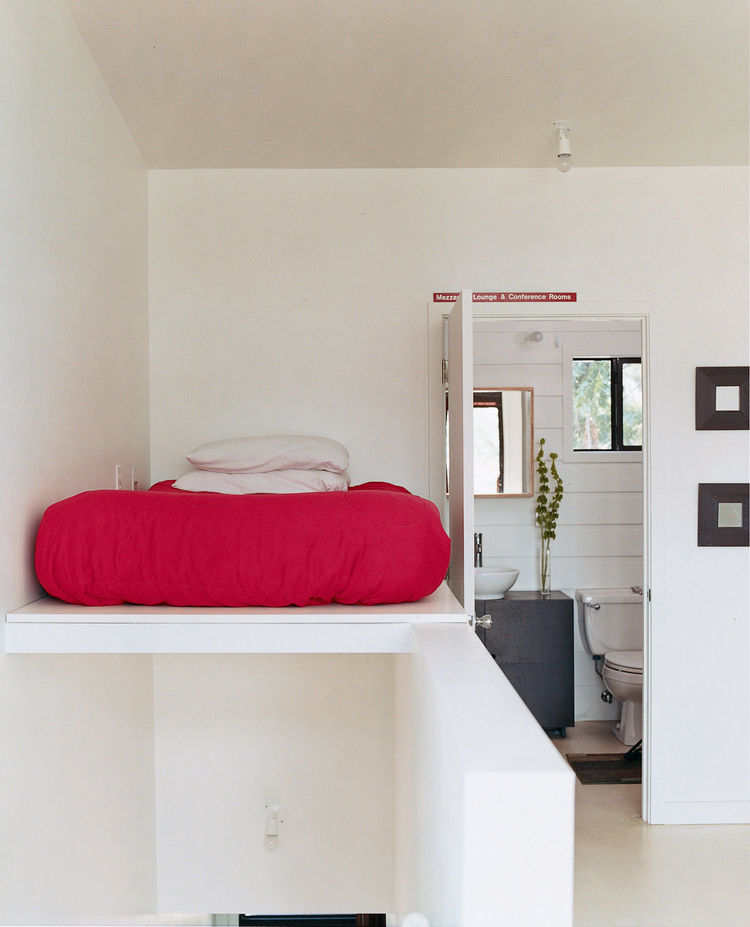 The bed is perched above the staircase leading from the second-story living area to  the third-story sleeping area.