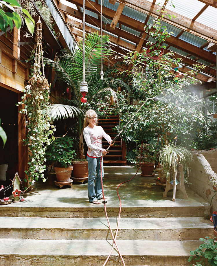 Sue waters the indoor foliage with an industrial hose hung from the ceiling.