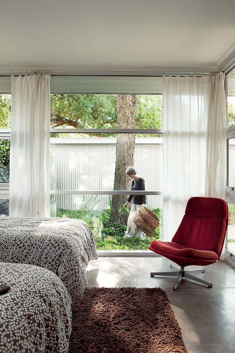 The guest room has one of the most enviable views of the pecan tree as well as the shed out back. Susan tends the ground cover. The Lunna swivel chair is from Ikea.