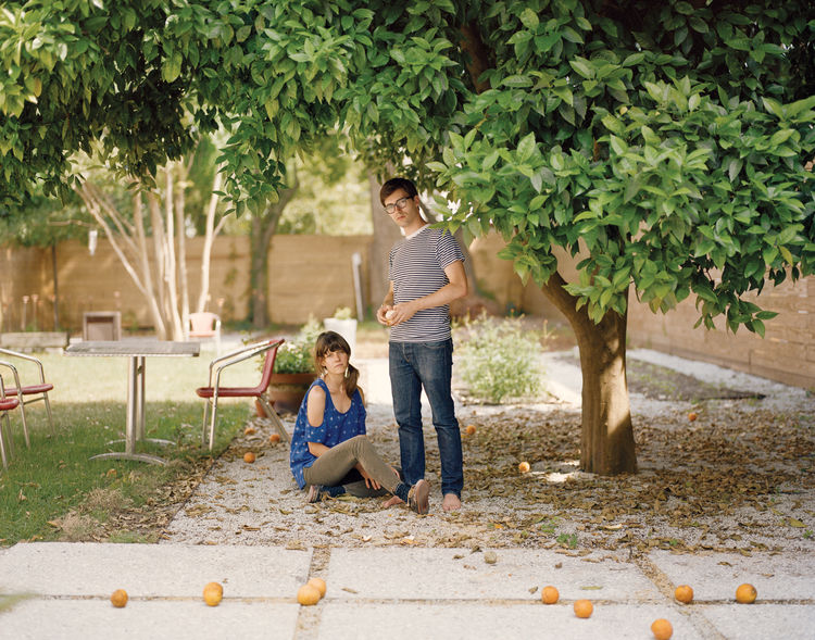 Josh Nissenboim and Helen Rice sitting under their orange tree in the yard of their residence.