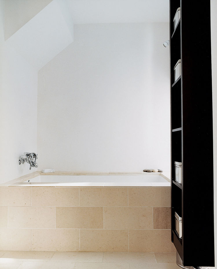 In the master bath, a Zuma tub with Hansgrohe fixtures is covered with limestone tile to soak up the sunshine.