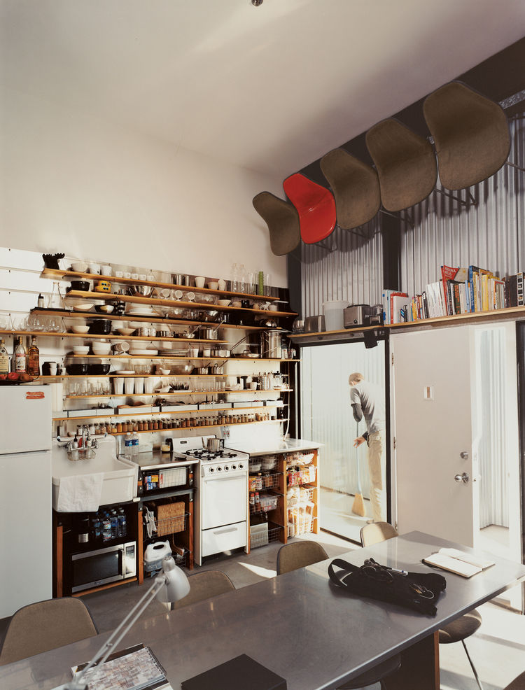 "The computer-designed kitchen area has the feel of a ship's galley, with everything neatly stowed, yet visible and instantly at hand: It's much the definition of ""ship-shape."" For dinner parties, well-worn Eames shell chairs are pulled down by David, with"