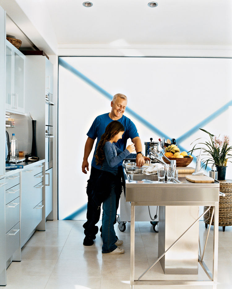Picard and his daughter, Alexis, who visits on weekends, enjoy cooking fresh ingredients like fish or artichokes in the Miele steam oven. The translucent glass wall provides plenty of natural light and gives the aluminum-and-stainless-steel kitchen a soft